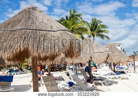 Close Up Of Coconut Palm Leaf Beach Umbrella With Unrecognizable Beachgoers Relaxing At A Distance I