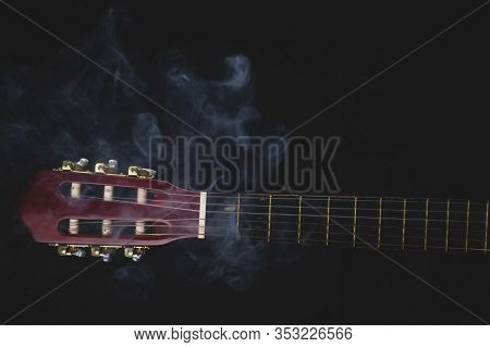 Guitar Headstock On Black Background. Acoustic Musical Instrument. Copy Space