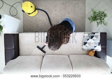 Woman In Apartment Cleans Sofa With Vacuum Cleaner. Wet Cleaning And Cleaning Upholstered Furniture