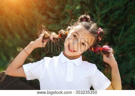 Lovely Smiling Child Girl Wearing White Shirt Having Fun Holding Her Pigtails In A Sunny Summer Park