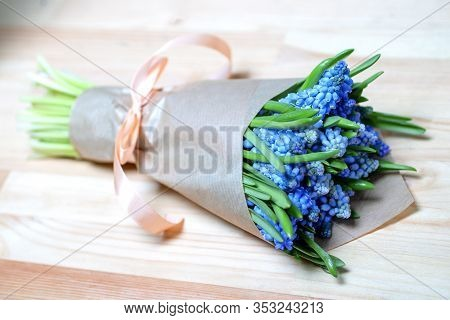 Bouquet With Blue Mouse Hyacinth In Kraft Paper On Wooden Background Closeup