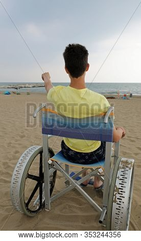 Boy On The Special Wheelchair With Big Wheels On The Beach With Yellow Tshirt