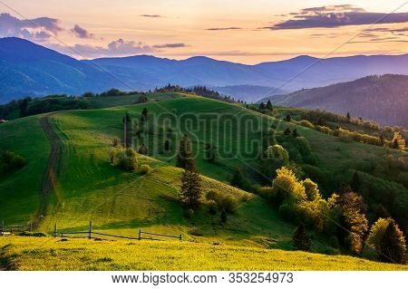 Mountainous Countryside In Springtime At Dusk. Road, Wooden Fence And Trees On The Rolling Hills. Ri