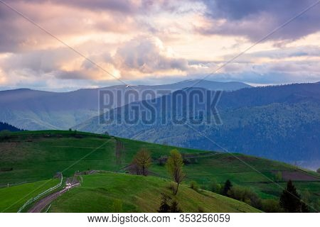 Mountainous Rural Area. Country Road Winding Through Agricultural Fields On Hills With Forest. Beaut