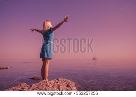 Rear View Of Happy Young Woman Blonde In Dress Raised Hands Up Standing On Stone Among Clear Calm Se