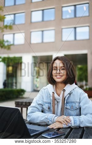 Vertical Portrait Smart Good-looking Female Student In Glasses Denim Jacket, Sit Outdoors On Bench,