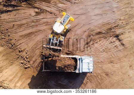 Excavators Loading Soil Onto An Articulated Hauler Truck.