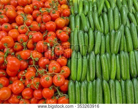 Half Red Tomatoes And Half Frame Of Green Cucumbers.