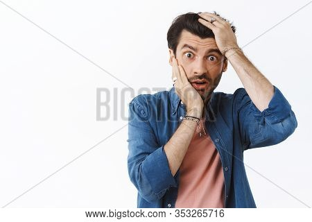 Shocked Concerned Young Man Stare Speechless And Distressed Camera, Grab Head With Both Hands And Ga