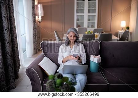 Progressive Lady With Two Gadgets And Wireless Earphones Stock Photo