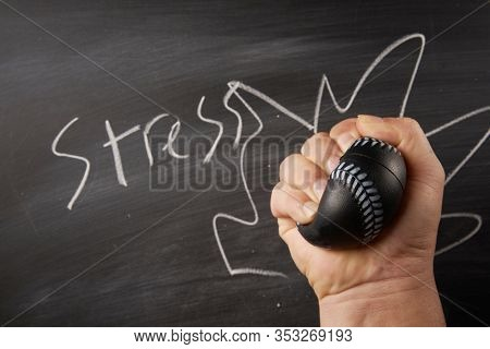 ball of stress relief in a hand on blackboard background