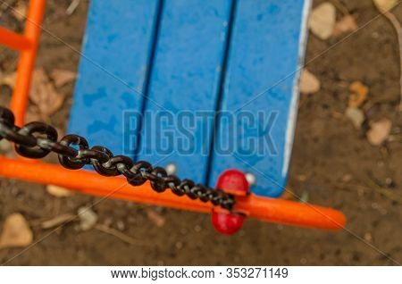 Empty Swing For Children On Chains. Top View Of A Swing Wet From The Rain. Focus On Chain Links. Clo