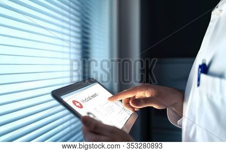 Doctor Using Electronic Medical Record (emr) In Tablet To Read Health Care Information For Patient.