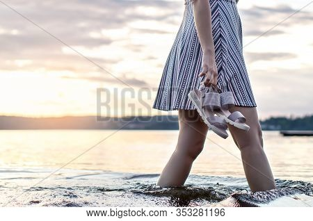Woman Walking In Lake Water In Finland On An Evening At Sunset Or Summer Night. Lady Holding Shoes I