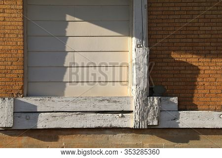 A Shipping Door At An Abandoned Brick Warehouse On A Sunny Afternoon With Shadows