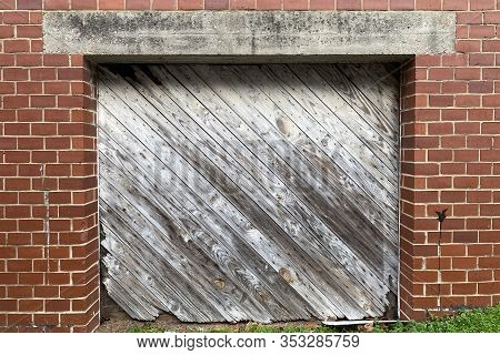 A Vintage Retro Diagonal Faded Wooded Shipping And Receiving Loading Dock Door On An Old Red Brick B