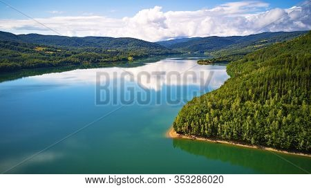 Reflection Of Sky, Clouds, Forest And Mountains In Water. Summer Landscape With Lake And Mountain Wo