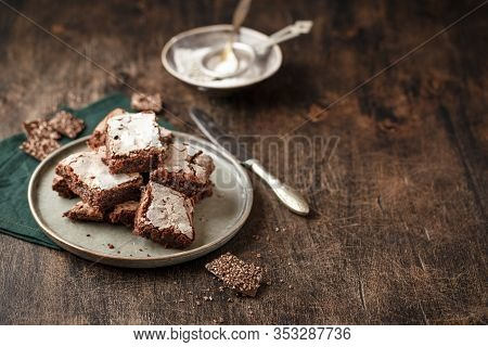Slices Homemade Brownie Cakes With Dark Chocolate Sprinkled With Icing Sugar On A Dark Background. P