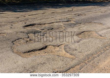 Big Potholes On A Damaged Asphalt Road