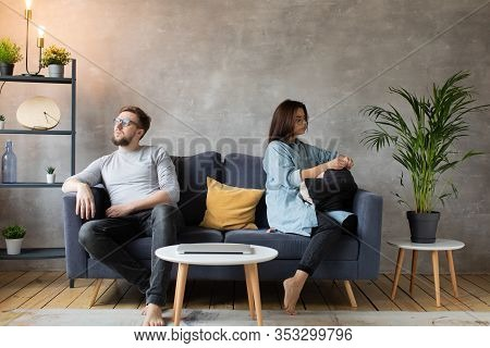 A Young Couple Are Sitting On The Couch After An Argument At Home. The Husband And Wife Sit With The