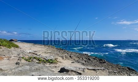 Fishing Poles Are Ready And Set On A Rocky Peninsula On Oahu, Hawaiis North Shore