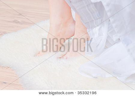 Women feet on a white fur