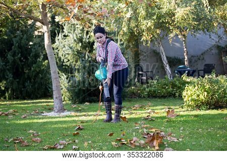 Pretty Young Woman Using Leaf Blower For Seasonal Works In Backyard
