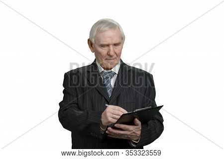Tax Inspector Wrinting Note On Clipboard. Old Man In Black Suit With Clip Board, White Isolated Back
