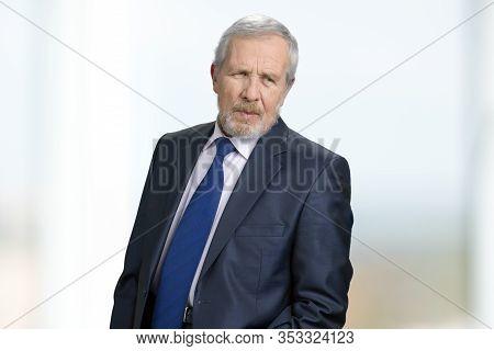 Portrait Of Serious Older Businessman In Suit. Unhappy Gaze Of Caucasian Senior Man. White Blurred B