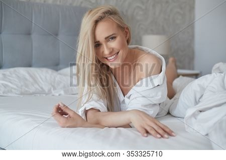 Beautiful middle aged woman lying on the bed, wearing white shirt and smiling, with her head resting upon her hand. Looking at camera.
