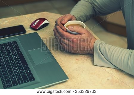 Cropped Shot Of A Mans Hands Holding A Cup Of Coffee Typing On A Laptop That Is On A Wooden Desk. Bu