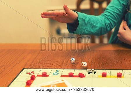 A Girl Playing A Board Game And Rolls Dice. Hand Throws The Dice On The Background Of Colorful Blurr