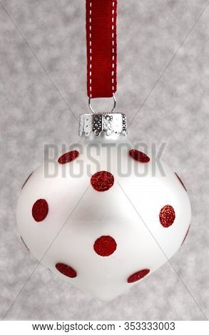 A Delicate Red And White Glittery Christmas Ornament Hanging On A Ribbon