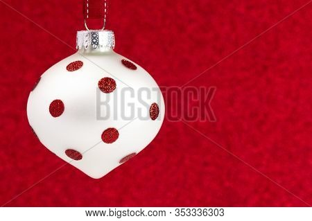 Delicate Red And White Glittery Christmas Ornament Hanging On A Ribbon