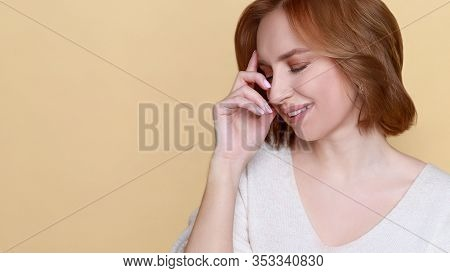 Pleasure Concept. Attractive Young Woman Holding Hand On Forehead With Closed Eyes, Smiles Joyfully