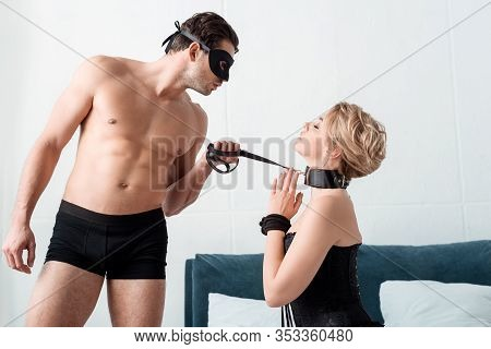 Side View Of Man In Eye Mask In Holding Bdsm Leash On Submissive Woman With Praying Hands
