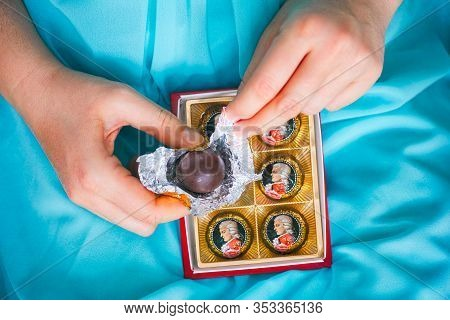 Tambov, Russian Federation - February 14, 2020 Woman Hands Open Mozart Candy From Candies Box.