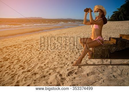 A Senior Asian Woman Wearing A Pink Bathing Suit, Wearing Glasses And Wearing A Straw Hat, With A No