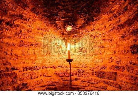 Burning Candle In A Dark Cellar Niche, Which Was Built With Bricks