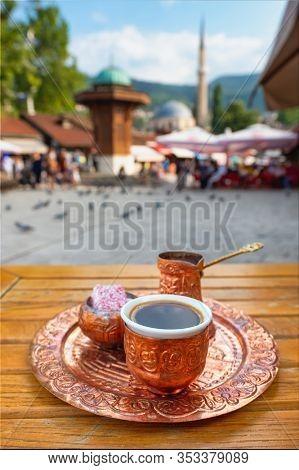 Traditional black bosnian coffee at Bascarsija square in old town of Sarajevo. Famous Sebilj fountain at Bascarsija square in old town of Sarajevo at background, BiH