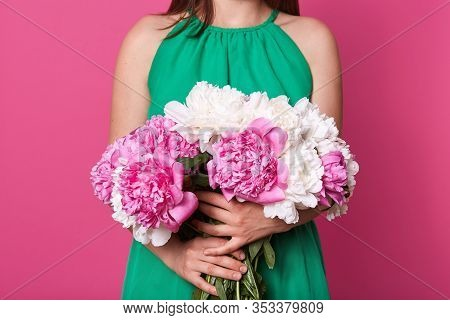 Faceless Portait Of Slim Woman Holds Beautiful Bouquet Of White And Pink Peonies In Front Of His Her