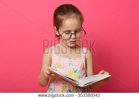 Image Of Little Girl Reading Interesting Book Isolated Over Pink Background, Female Kid Wearing Sund