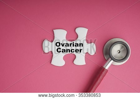 Ovarian Cancer Text With Stethoscope On White Jigsaw Puzzle Over Pink Background. Cancer Awareness C