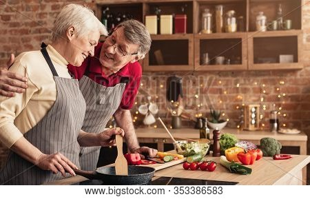 Enjoying Time Together. Happy Elderly Couple Embracing And Bonding With Each Other While Cooking Din