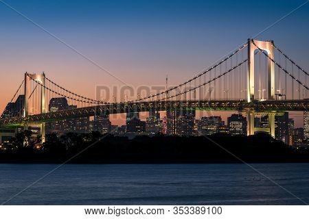 Rainbow Bridge With Night Illumination And Tokyo Cityscape. Tokyo Night Skyline