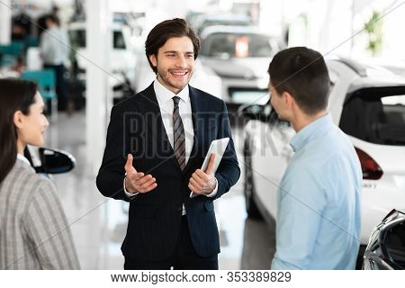 Car Sales Business. Auto Dealer Talking With Couple Clients, Selling Automobile, Holding Digital Tab