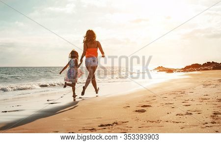 Happy Loving Family Mother And Daughter Having Fun On The Beach At Sunset - Mum Playing With Her Kid