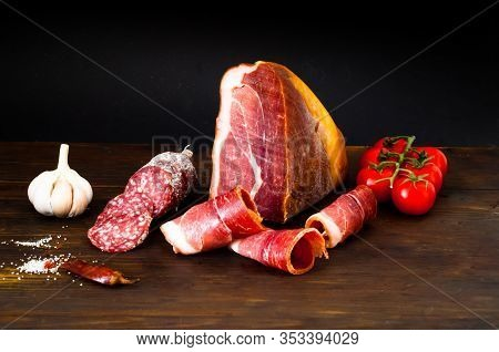 Authentic Italian Prosciutto Dry-cured On Wooden Background. Air-dried Ham And Organic Tomates. Clos