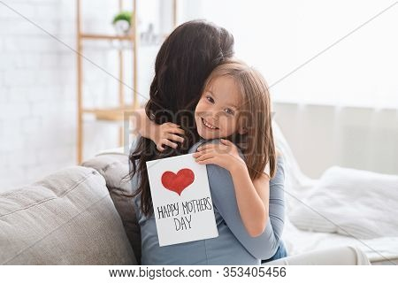 Smiling Little Daughter With Happy Mothers Day Gift Card Hugging Her Mom, Celebrating International
