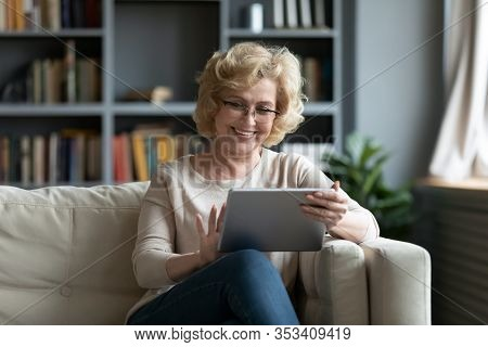 Middle-aged Woman Using Tablet Gadget At Home